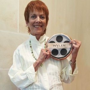 Catherine Wyler holds the exclusive Lights, Camera, Location make-up bag designed by House of Rouse